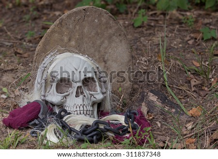 Grim reaper halloween prop on the ground with tombstone - stock photo