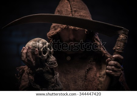 Grim Reaper is holding a skull and threatening. He is standing with a scythe - stock photo