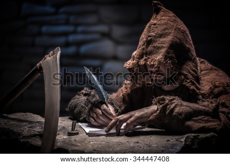 Grim Reaper is writing a list of his dead victims. The man is sitting near a scythe. He is holding a feather - stock photo