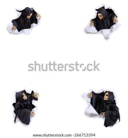 Grim reaper looking through hole torn in white paper - stock photo