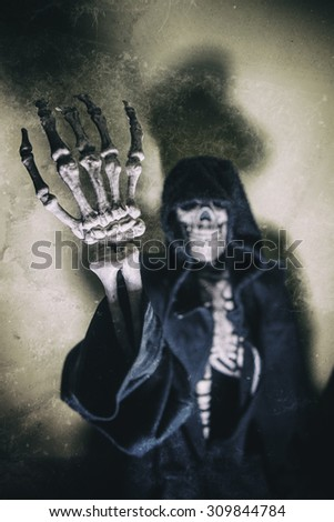 Grim Reaper Skeleton Hand. Skeleton in hoodie with empty hand reaching up, grim reaper concept. Shot with spot lighting and edited with vintage filters. - stock photo