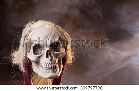 Grim reaper skull prop on a smoky background - stock photo