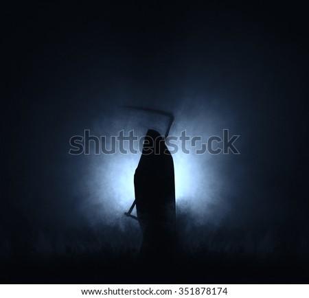 Grim reaper, the death itself, scary horror shot of Grim Reaper in fog holding scythe. - stock photo