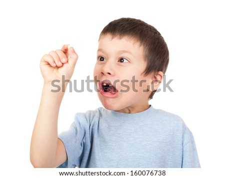 grimacing boy looks at lost tooth