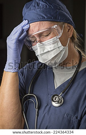Grimacing Female Doctor or Nurse Wearing Protective Facial Wear and Surgical Gloves. - stock photo