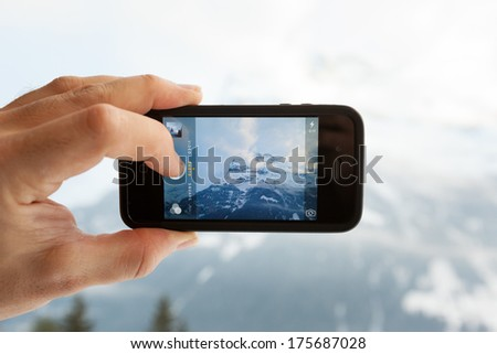 GRINDELWALD, SWITZERLAND - FEBRUARY 4, 2014: Man taking a photo of the Eiger mountain using the camera app on an Apple iPhone 4s. Close-up shot of the hand holding the phone with the mountain behind. - stock photo