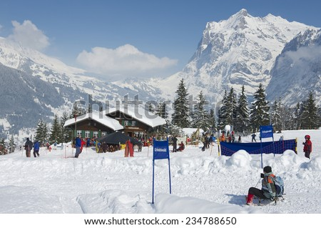 GRINDELWALD, SWITZERLAND � MARCH 07, 2009: Unidentified tourists relax at the Brandegg ski station in Grindelwald, Bernese Alps, Switzerland. Grindelwald area is a famous ski resort in Switzerland. - stock photo