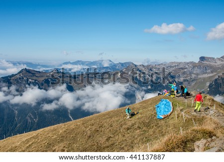 GRINDELWALD, SWITZERLAND - SEPTEMBER 30, 2015 : Unidentified   paragliders at Mannlichen top point above Grindelwald, Switzerland.