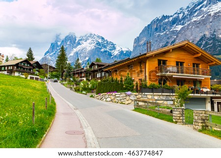 Grindelwald valley with village scattered on the green slopes of Bernese Alps. Grindelwald village in Switzerland is a popular gateway for skiing in winter and hiking in summer.