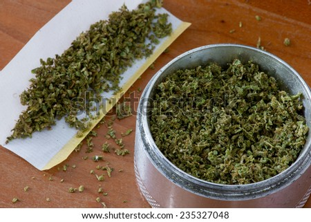 Grinder and papers for rolling a marijuana cigaretter - stock photo