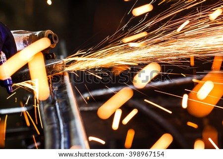 grinding machine on work and spark movement in the automotive parts industry - stock photo