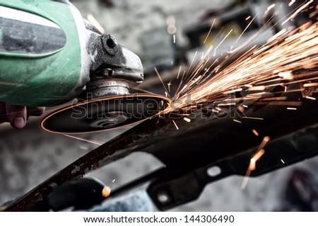 grinding through metal in steel factory - stock photo