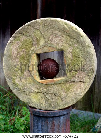 Grindstone on a rusty pedestal, with an old cannon ball in center. - stock photo