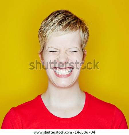 Grining young woman with her eyes closed on a yellow background - stock photo