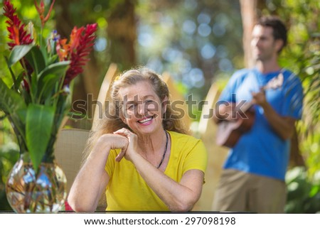 Grinning adult female listening to musician in Hawaii