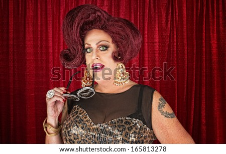 Grinning drag queen biting sunglasses in theater - stock photo