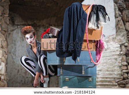 Grinning female clown squatting near stack of suitcases - stock photo