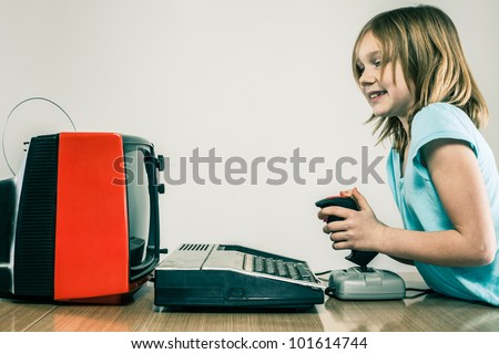 Grinning girl on old style gaming set up with analog television set and vintage joystick