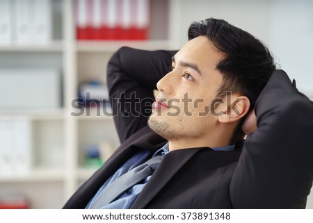 Grinning handsome young Asian salesman in blue suit and tie leaning back with arms behind head as he looks upward - stock photo