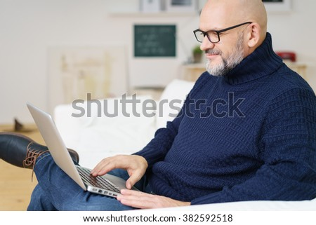 Grinning middle aged bald and bearded attractive man in blue sweater typing on metallic finish laptop while seated on sofa - stock photo