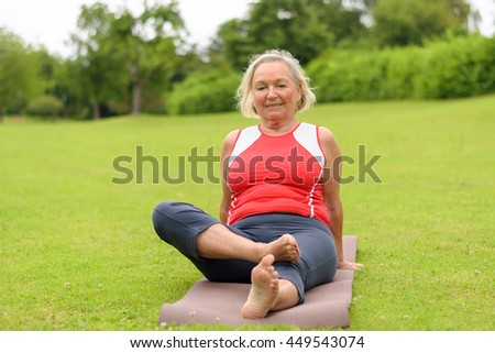 Grinning senior woman sitting on yoga mat outdoors in park with wide open field of green turf grass and copy space - stock photo