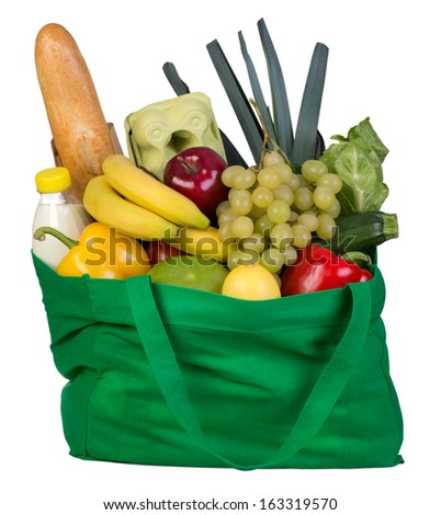 Groceries in green bag isolated on white background - stock photo