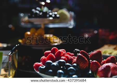 Grocery decoration. Tasty berries illuminated by arificial lights in a dark room - stock photo
