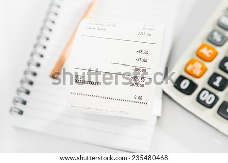 Grocery shopping list on notebook with calculator and pencil - money account management concept