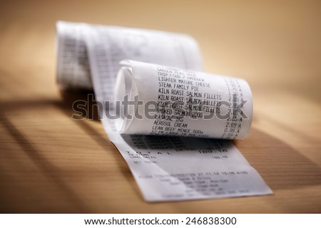 Grocery shopping list till roll printout on a wooden table - stock photo