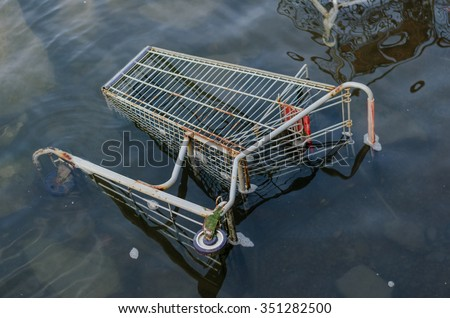 Grocery store shopping cart sits in clear water after being taken away by flooding - stock photo