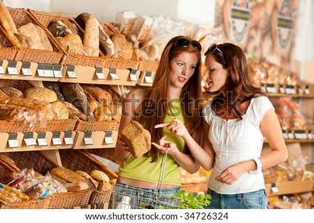 Grocery store: Two women choosing bread at bakery - stock photo