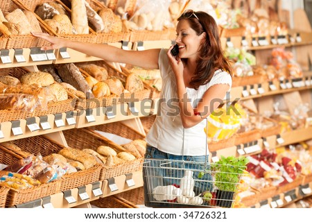 Grocery store: Young woman holding mobile phone and shopping basket - stock photo