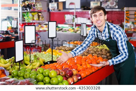 Grocery worker selling seasonal fruits in farm food store