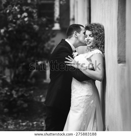grom huging kissing bride with red hair near wall outdoors Lviv