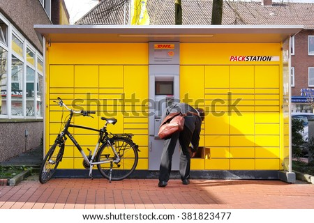 GRONAU, GERMANY - FEBRUARY 23, 2016: Customer pick-up his mail at a DHL automated parcel collection point. DHL is a trade name of Deutsche Post DHL, a German courier company and world's largest.