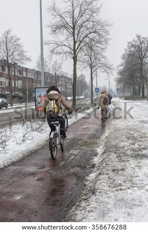 GRONINGEN-JAN 5:People walking and biking on a bike path in the Netherlands during heavy glaze on the ground on January 5, 2015 - stock photo