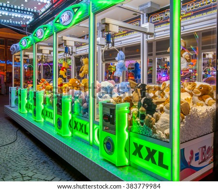 GRONINGEN, THE NETHERLANDS-MAY 5, 2015: Arcade crane vending machine with colourful green lights on the annual funfair on central square. - stock photo