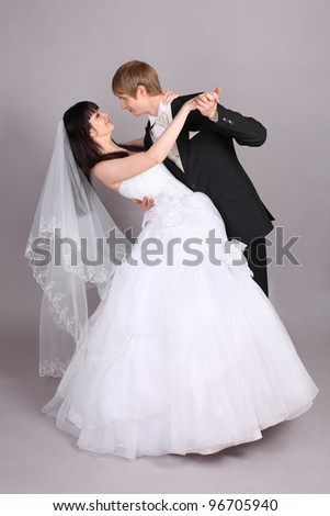 Groom and beautiful bride dance in studio on gray background - stock photo
