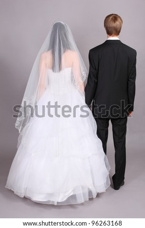 Groom and beautiful bride stand their backs to camera in studio on gray background - stock photo