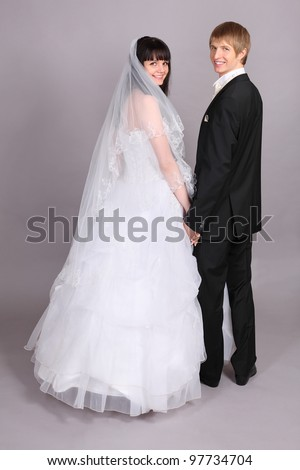 Groom and beautiful bride turned and look into camera in studio on gray background