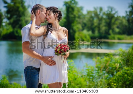 Groom and Bride against the background of water in a park. Love story of happy couple. wedding dress. Bridal wedding bouquet of flowers. feelings, relations, passion - stock photo