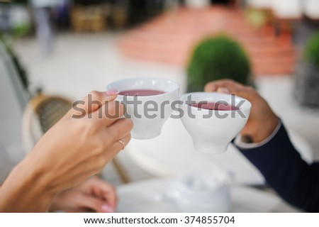 Groom and bride are drinking red tea outdoors.