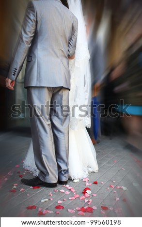 Groom and bride are holding hand of each other with feelings of love. Confetti from colorful petals are lying at the ground. - stock photo