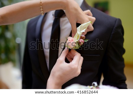 Groom and bride are wearing a boutonniere indoors. Male portrait of handsome guy. Beautiful model boy in colorful wedding clothes. Man is posing - stock photo