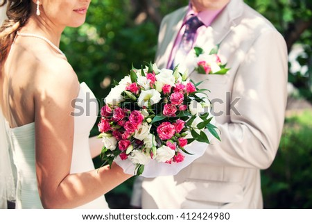 groom and bride holding in her hand a pink bridal bouquet - stock photo
