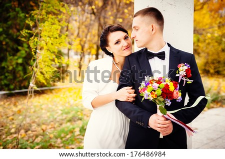 Groom and Bride in a park. Young couple kissing in wedding gown. wedding dress. Bridal wedding bouquet of flowers - stock photo