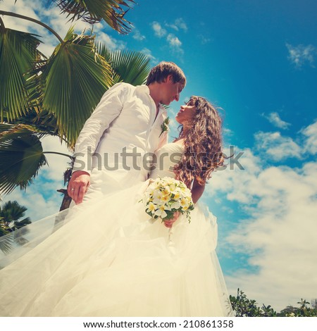 groom and bride in white with a wedding bouquet with frangipani flowers on a background of palm trees and blue sky in the Seychelles - stock photo