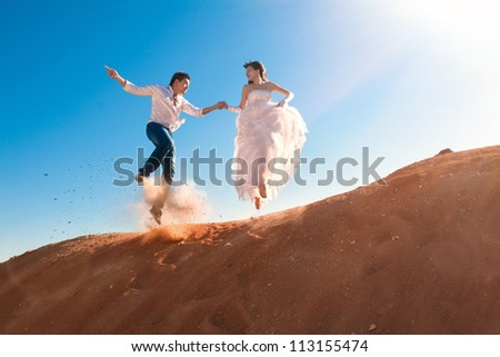 groom and bride jumping - stock photo