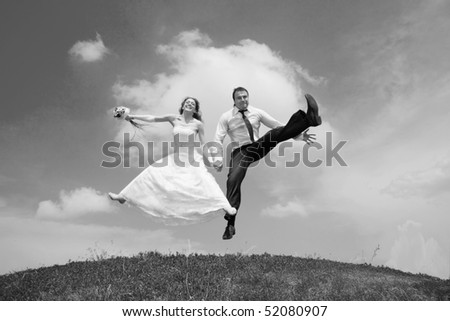 Groom and bride jumping against backdrop a sky. In all growth.