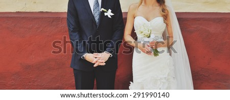 Groom and bride next to red wall. Wedding  couple together. - stock photo